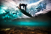 Underwater view of surfer falling through water after catching a wave on a shallow reef in Bali, Indonesia