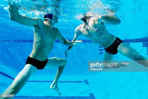 Underwater view of two men swimming and playing water polo
