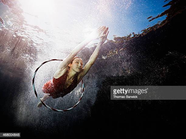 Underwater view of woman diving through hoop