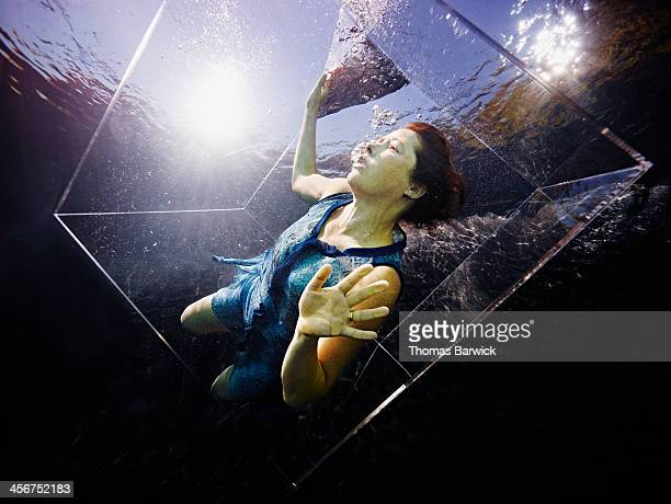 Underwater view of woman in glass box looking up