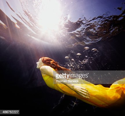 Underwater view of woman swimming to surface
