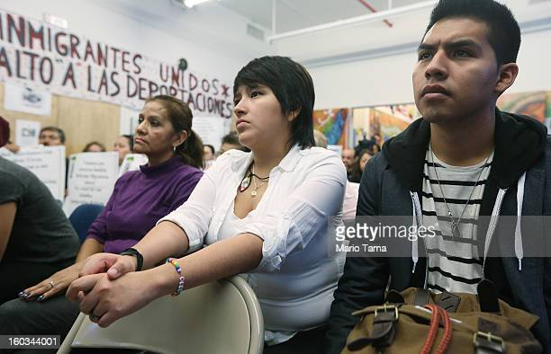 Undocumented immigrant Oscar Rodriguez originally from Mexico watches with Yenny Quispe who is from Peru and received her Green Card two days ago...