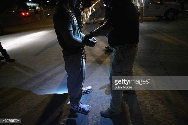 Undocumented immigrants are shackled before boarding an Immigration and Customs Enforcement charter jet early on October 15 2015 in Mesa Arizona The...