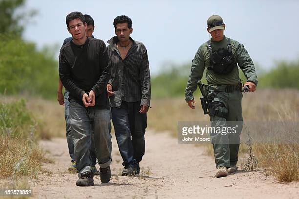 Undocumented immigrants await transportation to a processing center after being caught by US Border Patrol agents some 60 miles north of the USMexico...