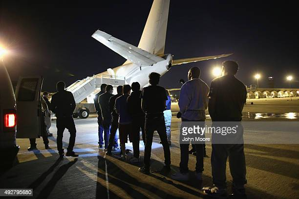 Undocumented immigrants wait to be loaded onto an Immigration and Customs Enforcement charter jet early on October 15 2015 in Mesa Arizona The...