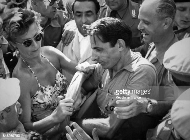 Une belle fan de Fausto Coppi l'aide à vêtir le nouveau maillot après l'tape de Sestrières Italie en 1952