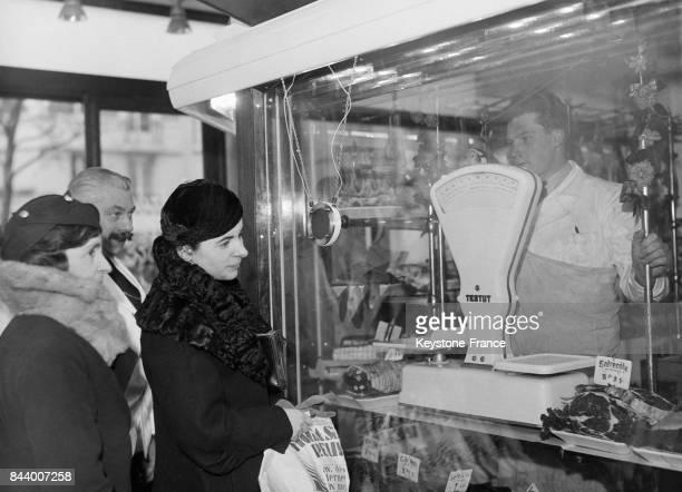 Une boucherie moderne est équipée d'une vitre séparant le boucher et la viande de ses clients avec lesquels il communique par le moyen d'un...