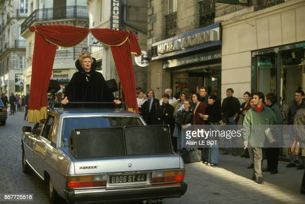Une cantatrice chante debout dans une voiture decapotable entouree d'un rideau rouge c'est l'opera mobile du Festival des Allumes le 22 octobre 1993...