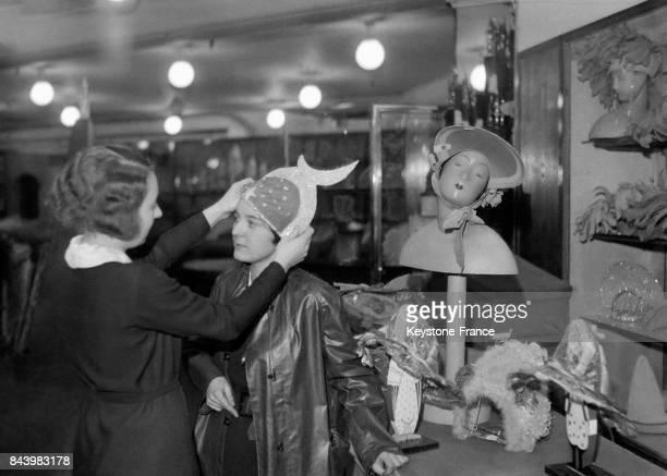 Une catherinette essaie un chapeau chez un couturier en prévision de la fête de SainteCatherine le 22 novembre 1932 à Paris France