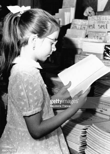Une écolière lit un livre dans une librairie du Quartier Latin quelques jours avant la rentrée scolaire le 2 septembre 1961 à Paris France