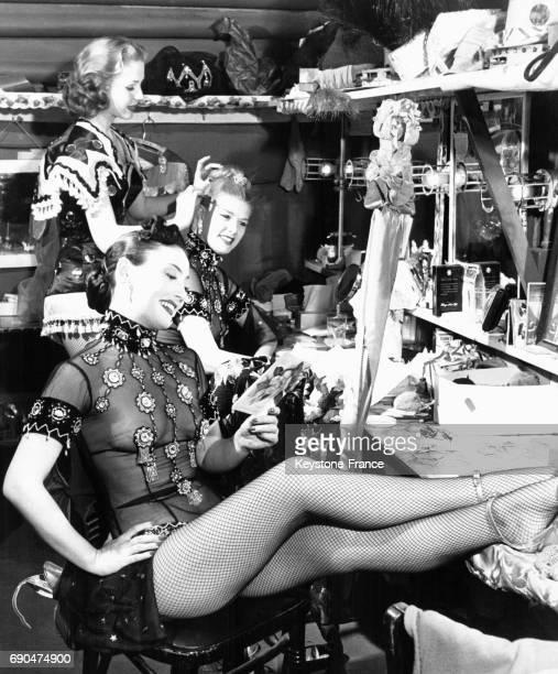 Une danseuse de revue arrange les cheveux d'une de ses partenaires pendant qu'une troisième jeune femme lit une carte qu'elle vient de recevoir entre...