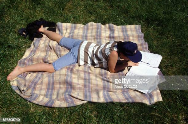 Une etudiante a l'Universite revise ses cours allongee dans l'herbe le 1 juin 1994 Orsay France