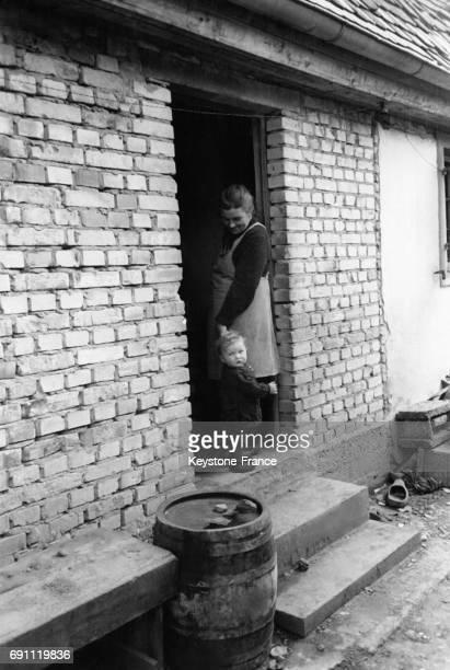 Une femme allemande et son jeune fils sur le pas de sa porte lors de l'entrée des troupes françaises en Allemagne