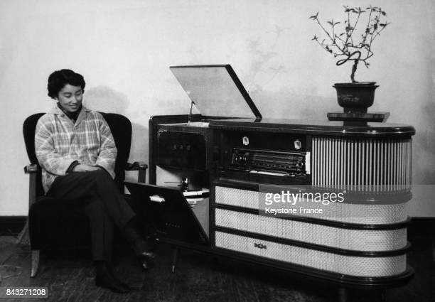 Une femme chinoise écoute la radio sur un poste de radio qui fait également office de gramophone et de magnétophone créé par l'entreprise Panda le 8...