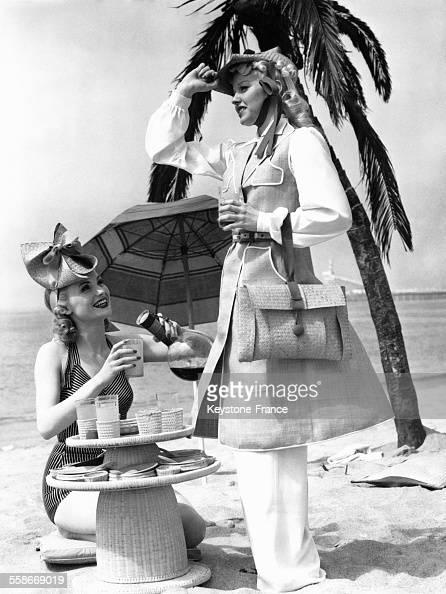 ... femme en maillot de bain assise sur le sable et préparant une boisson