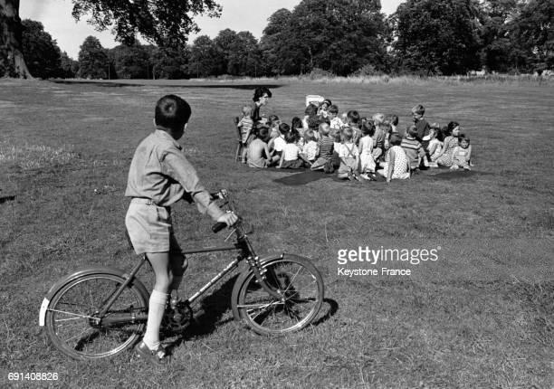 Une femme faisant la lecture à un groupe d'enfants dans un parc durant leurs vacances le 26 août 1964 à Birmingham RoyaumeUni