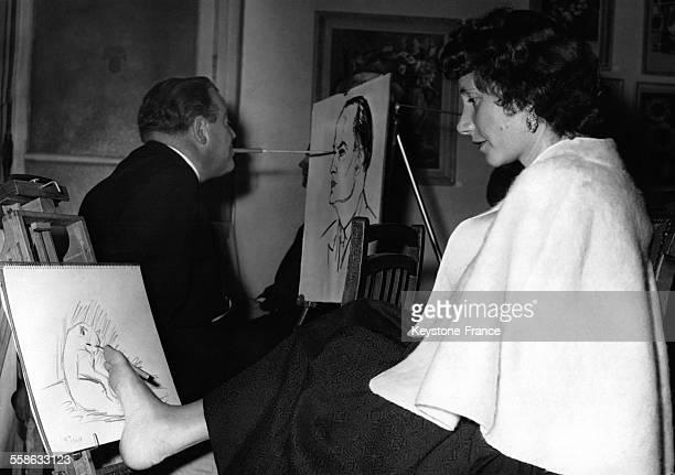 Une femme peint avec son pied et un homme avec sa bouche dans un atelier de peinture