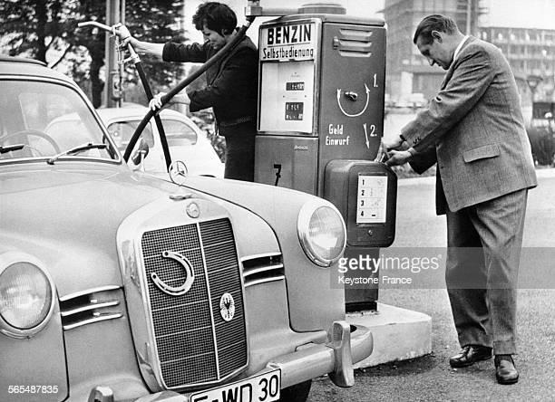 Une femme tenant le pistolet pour faire le plein alors que l'homme met l'argent dans le distributeur en Allemagne le 8 août 1959