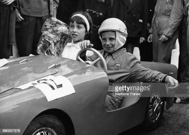 Une fillette tenant un bouquet de fleurs assise à côté d'un garçon portant une combinaison et un casque au volant d'un cabriolet sur la piste du...