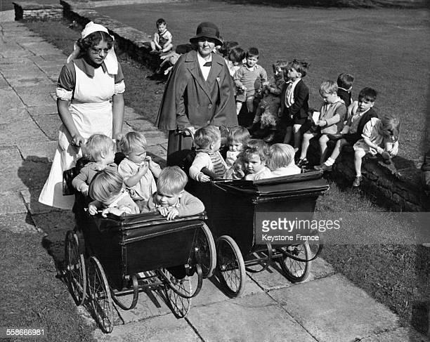 Une infirmière et une gouvernante poussent chacune un landau de quatre enfants pendant que les plus grands jouent assis sur un muret non loin d'elles...