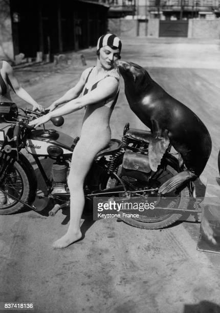 Une jeune artiste en combinaison sur sa moto se retourne pour embrasser un lion de mer assis derrière elle le 6 avril 1932