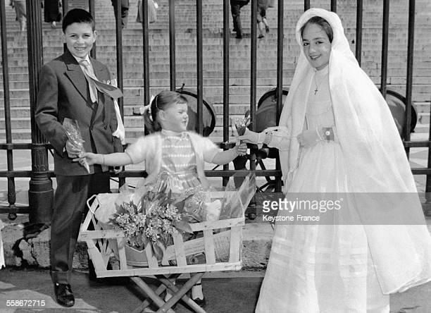 Une jeune communiante et un jeune garçon achètent du muguet à une toute petite fille devant l'Eglise de la Madeleine le 1er mai 1959 à Paris France