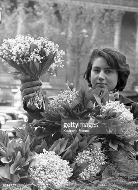Une jeune femme et son étal de muguet le 1er mai 1960 à Paris France