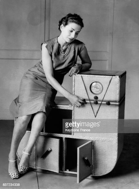 Une jeune femme présente un poste de radio équipé d'un minibar et d'une étagère pour livres à Radiolympia le 24 août 1937 à Londres RoyaumeUni