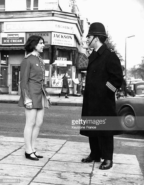 Une jeune femme vêtue d'une veste d'uniforme face à un policier britannique sur Portobello Road circa 1950 à Londres RoyaumeUni