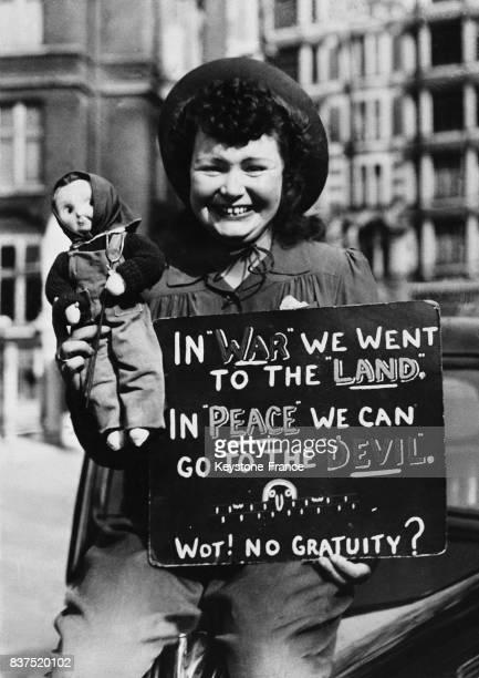 Une jeune manifestante et son fétiche présente une pancarte sur laquelle on peut lire 'Pendant la guerre nous avons assuré le retour à la terre...