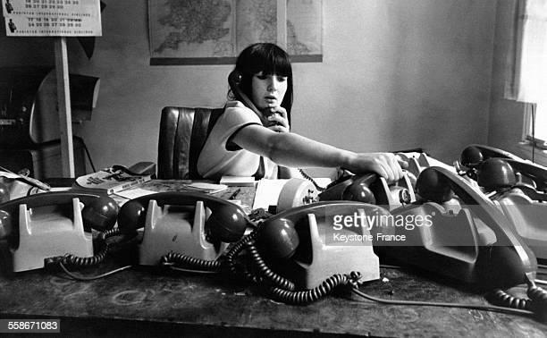 Une jeune opératrice répond à plusieurs téléphones aux bureaux Wolbeck Minicab de Paddington Street le 14 juin 1966 à Londres RoyaumeUni