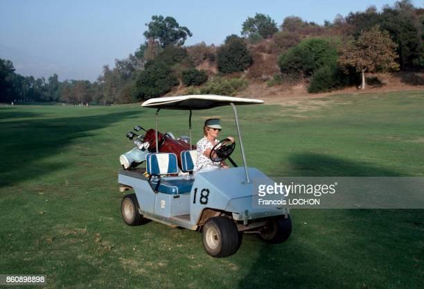 Une joueuse de golf conduit une voiture électrique sur un terrain de golf en octobre 1980 EtatsUnis