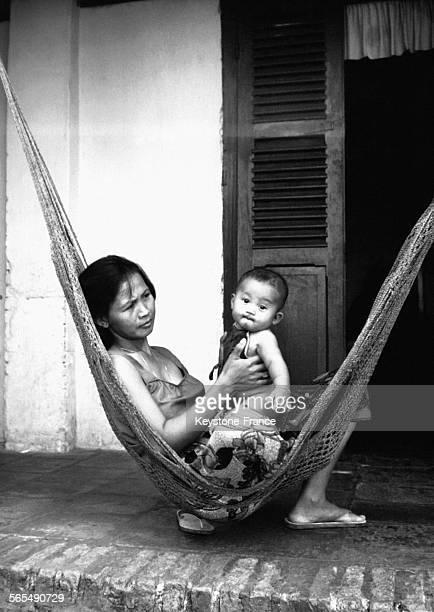 Une mère tient son jeune garçon dans les bras devant une maison au Cambodge le 14 août 1969