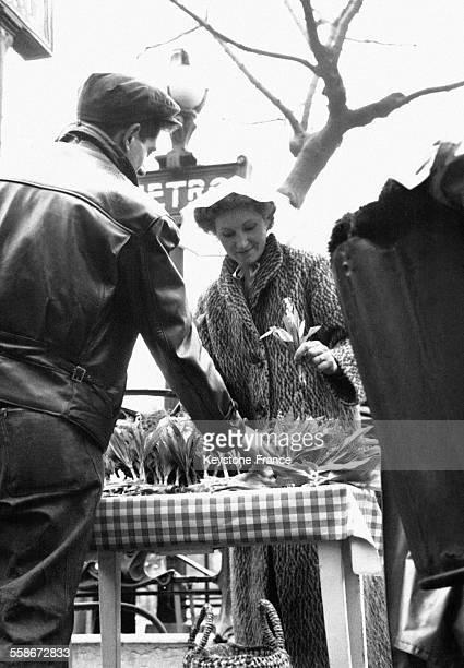 Une Parisienne coiffée d'un chapeau achète du muguet à un vendeur de rue à la sortir du métro circa 1950 à Paris France