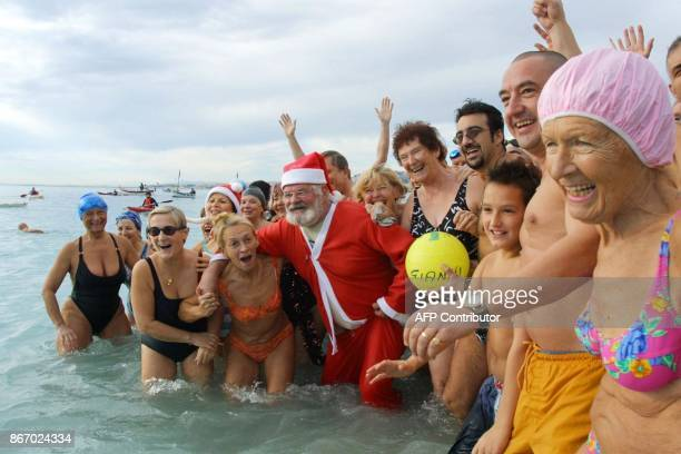 une personne déguisée en Père Noël se baigne aux côtés de quelque deux cents participants le 15 décembre 2002 à Nice lors du traditionnel bain de...