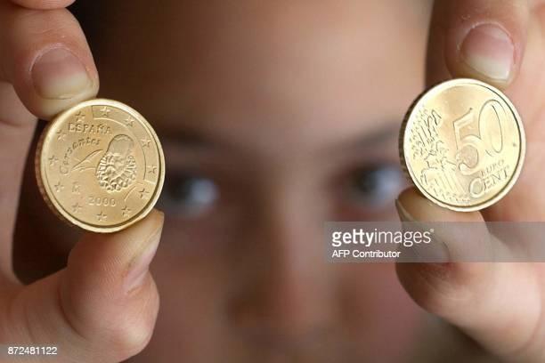une personne montre le 15 décembre 2001 à Madrid les côtés recto et verso d'une pièce espagnole de 50 centimes d'euro à l'effigie de l'écrivain...