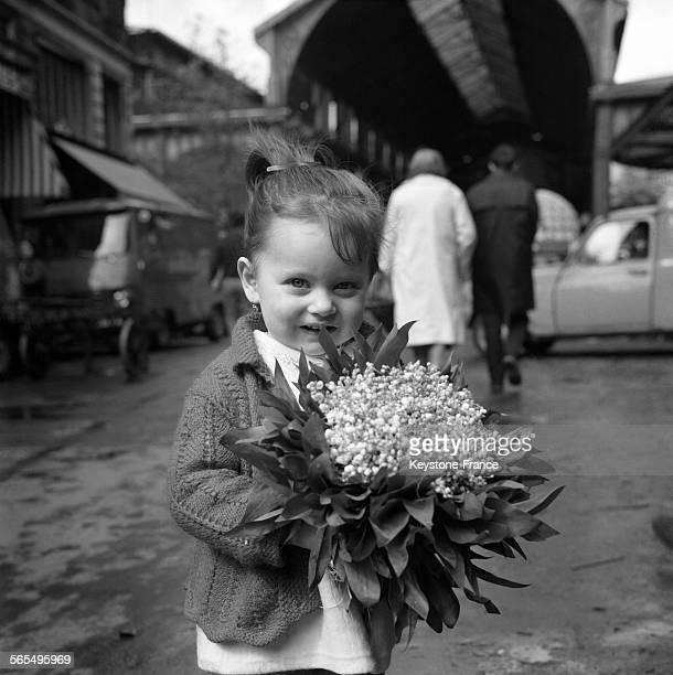 Une petite fille avec un bouquet de muguets dans les mains à Paris France le 30 avril 1968