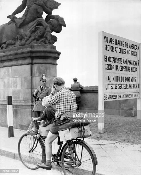 Une petite fille est assise sur la bicyclette de son père sur le pont marquant la fin du secteur américain de Berlin Allemagne en 1945