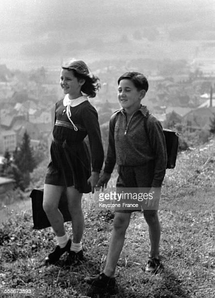 Une petite fille et un petit garçon sur le chemin de l'école à travers la campagne en Allemagne
