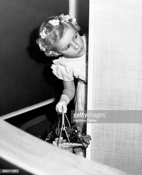 Une petite fille habillée en demoiselle d'honneur risque un coup d'oeil derrière un rideau son panier de fleurs à la main à Caterham RoyaumeUni
