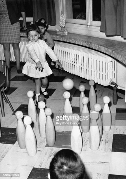 Une petite fille joue aux quilles lors de la rentrée scolaire en maternelle en France le 15 septembre 1967