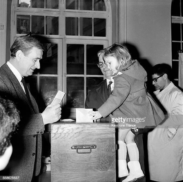 Une petite fille met le bulletin de vote de son papa dans l'urne lors du deuxieme tour des elections municipales le 21 mars 1965 a Paris France