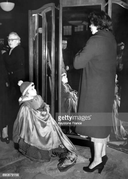 Une petite fille porte le manteau de sa mère pendant que cette dernière essaie un nouveau en solde au magasin John Barkers sur Kensington à Londres...
