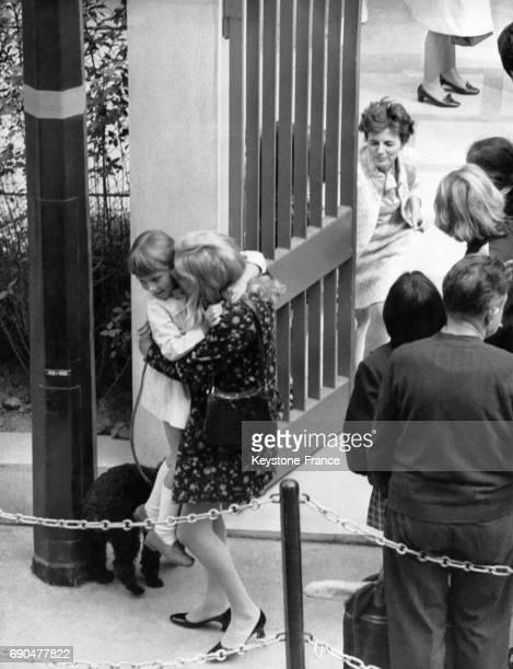Une petite fille retrouve sa mère en souriant à la sortie du premier jour de classe le 8 septembre 1969 en France
