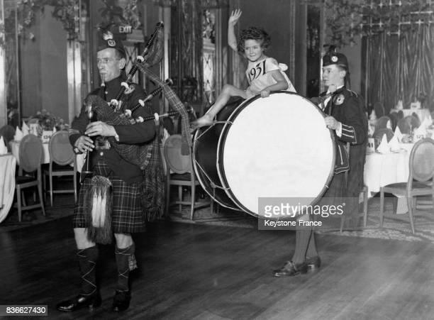 Une petite fille s'amuse perchée sur la grosse caisse d'un musicien écossais derrière un joueur de cornemuse lors des préparatifs dans une salle de...