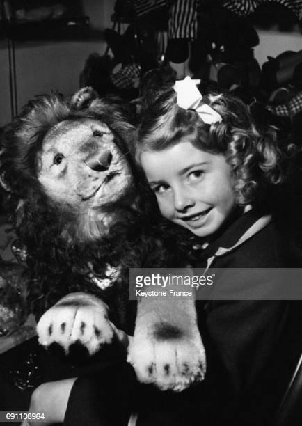 Une petite fille tient un lion en peluche dans un magasin de jouets