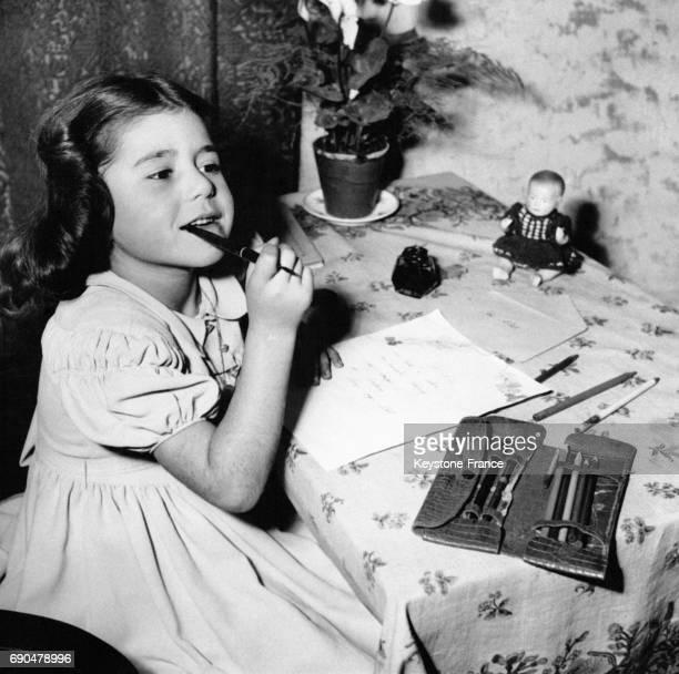 Une petite fille un stylo à la bouche réfléchit à la façon de rédiger sa lettre au Père Noël le 2 décembre 1948 en France