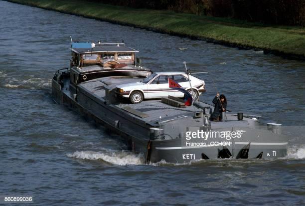 Une péniche chargée d'une voiture descend le canal de l'Oise en novembre 1981 France