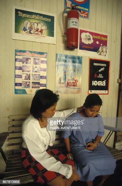 Une prostituee recoit des conseils pour se proteger du sida en juin 1994 en Thailande