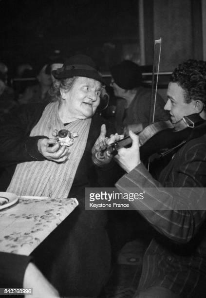 Une vieille dame invitée à un repas offert pour les Vieux nécessiteux écoute avec bonheur l'air que lui joue un jeune violoniste à Paris France le 1...